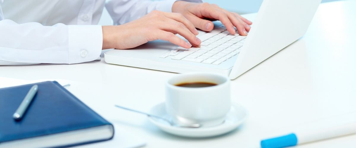 woman typing on a white laptop with a book and a coffee cup.