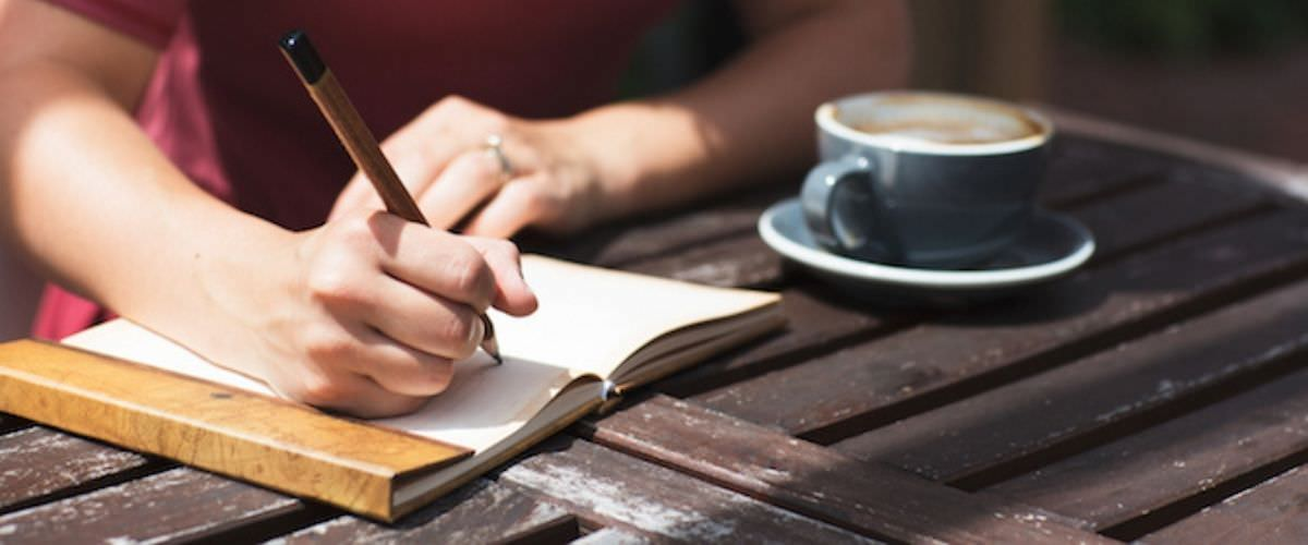 woman writing in a journal on a brown table with a cup of coffee.